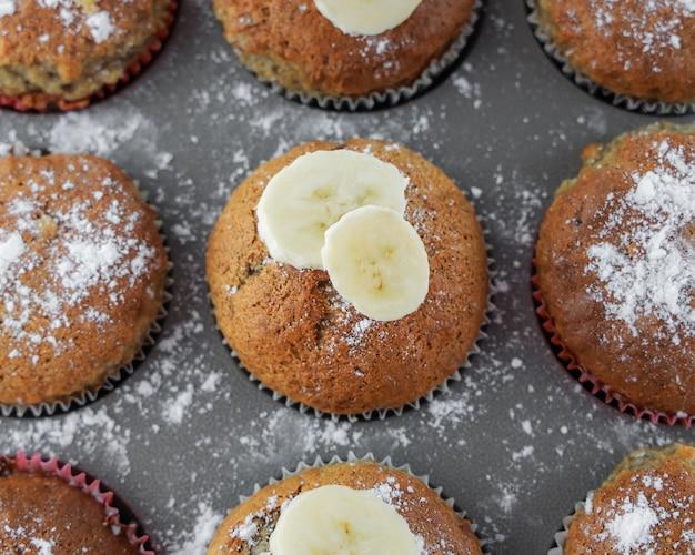 Achtergrond, zelfgemaakte muffins bakken met banaan in grijze bakvorm