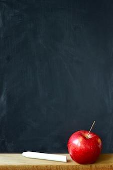 Achtergrond zwart bord met krijt vlekken krijtbord en rode appel, copyspace