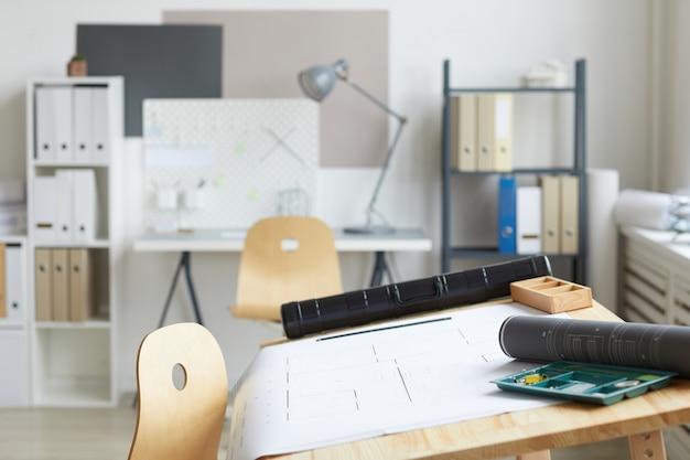 Achtergrondafbeelding van architecten werkplek met tekentafel en tools op voorgrond,