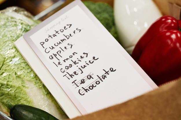 Achtergrondafbeelding van boodschappenlijstje op krat met verse biologische groenten, voedsel en boodschappen concept, kopieer ruimte