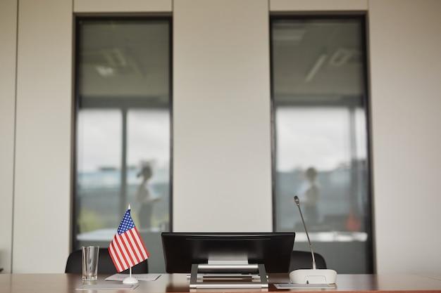 Achtergrondafbeelding van de amerikaanse vlag op tafel in lege vergaderruimte tijdens internationale of politieke zakelijke evenement,