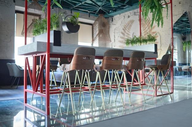 Achtergrondafbeelding van eco-vriendelijk café-interieur met focus op barstandaard en stoelen versierd met groene planten, kopieer ruimte