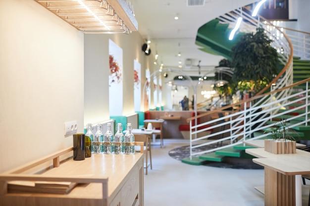Achtergrondafbeelding van eco-vriendelijk café-interieur met focus op wenteltrap versierd met groene planten, kopieer ruimte