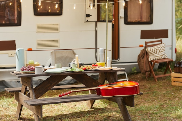 Achtergrondafbeelding van een gezellige buitencamping met picknicktafel en aanhangwagen ingericht door sprookjesachtige...