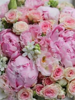 Achtergrondafbeelding van een mooie bloemen het boeket van roze pioenrozen eustoma en witte oxypetalum