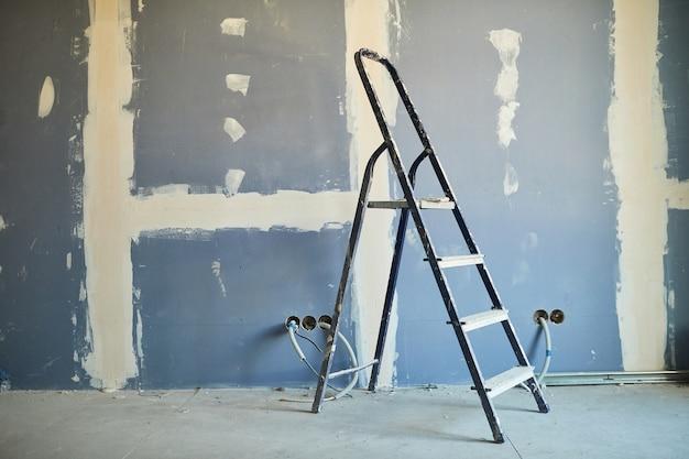Achtergrondafbeelding van gebruikte ladder tegen droge muur op bouwplaats of het bouwen van huis, exemplaarruimte