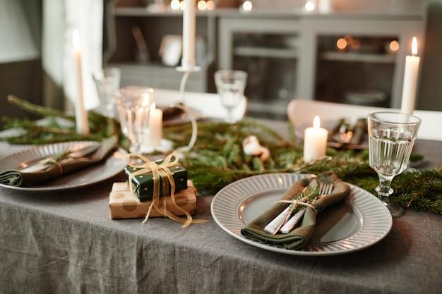 Achtergrondafbeelding van gezellige eetkamer ingericht voor kerstmis met kaarsen aangestoken en verse dennentakken...