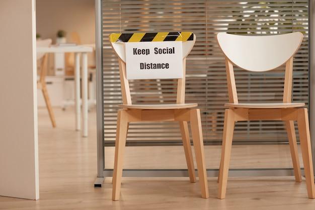 Achtergrondafbeelding van houten stoelen voor het wachten in de rij in kantoor met keep social distance-teken, kopieer ruimte