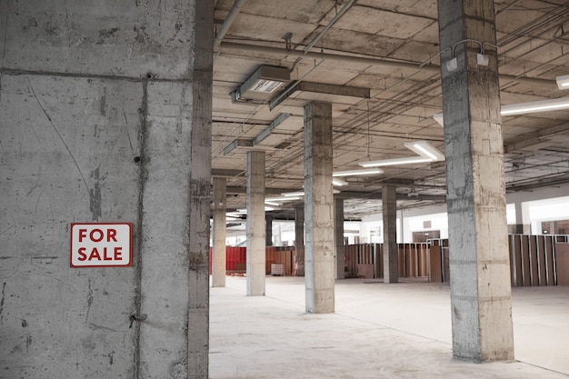 Achtergrondafbeelding van leeg gebouw in aanbouw met betonnen kolommen en te koop bord,