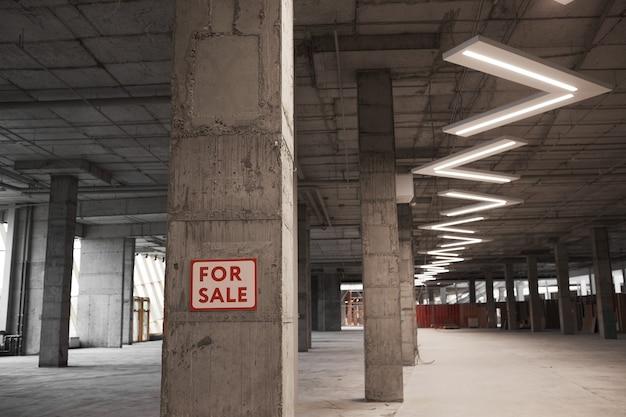 Achtergrondafbeelding van leeg gebouw in aanbouw met te koop bord op betonnen kolom en grafische plafondlampen,