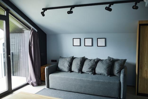 Achtergrondafbeelding van minimaal huisinterieur met focus op gezellige bank in diepblauwe kleur, kopieer ruimte