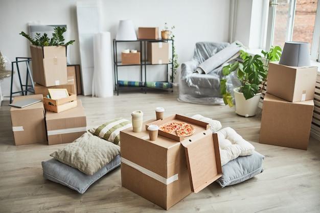 Achtergrondafbeelding van pizza op kartonnen doos als geïmproviseerde tafel in lege ruimte terwijl familie verhuist...