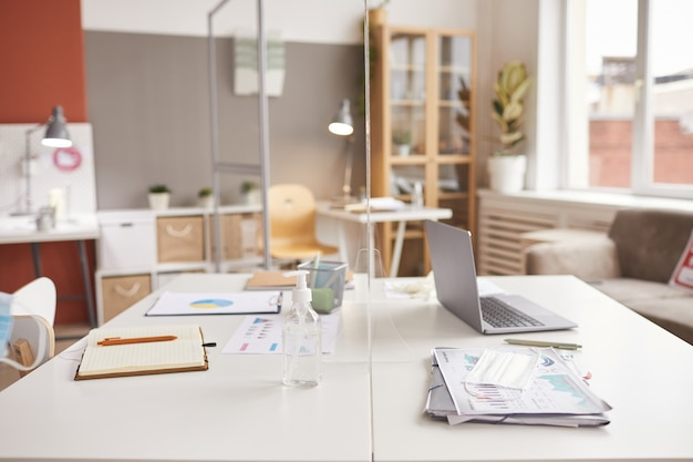 Achtergrondafbeelding van twee bureaus gescheiden door glazen ruit op post pandemie werkplek, kopie ruimte
