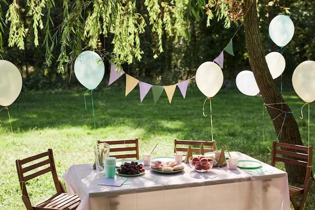 Achtergrondafbeelding van zomer picknicktafel buiten versierd met ballonnen voor verjaardagsfeestje kopieerruimte