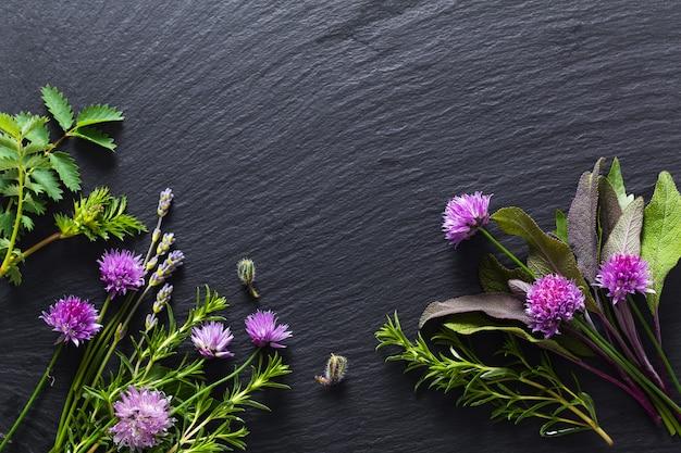 Achtergrondconcept voor voedsel of schoonheidsreclame door bieslookbloesems en aromatische kruiden binnen op de zwarte raad van de leisteen met exemplaarruimte