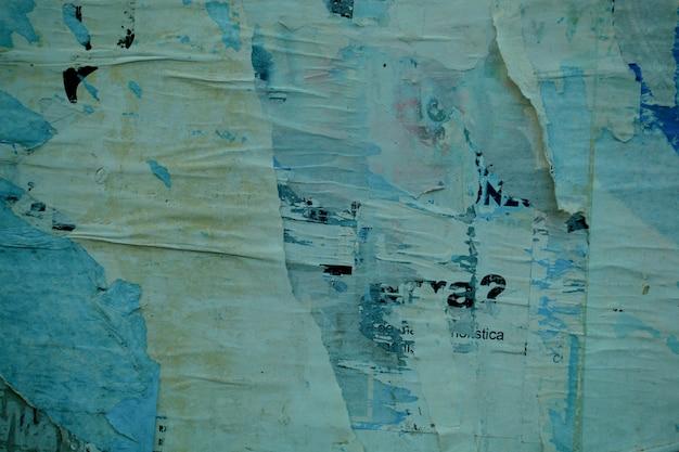 Achtergrondstructuur van de rest van oude posters en mededelingen op een muur met stroken overlappend gescheurd papier