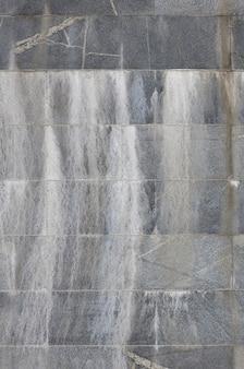Achtergrondtextuur van een muur van oude grijze graniettegels