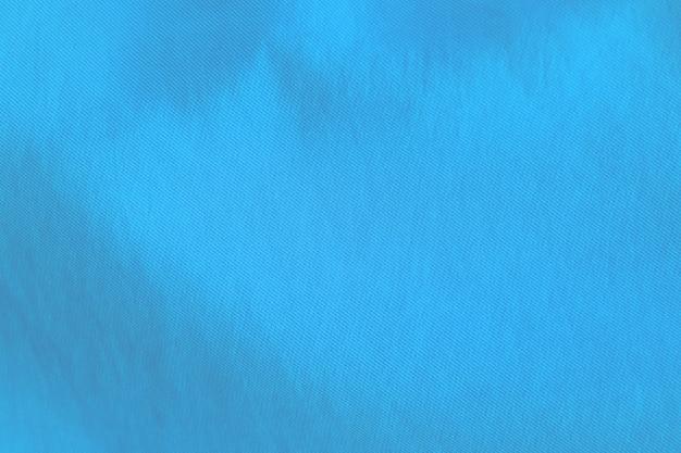 Achtergrondtextuur van golvend blauw katoen.