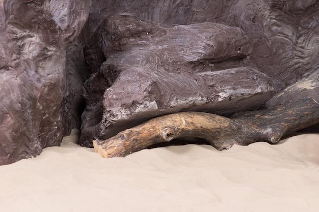 Achtergrondtextuur van ruwe grijze kunstmatige rotsen met drijfhout en gouden zeezand op een strand in een display of tentoonstelling
