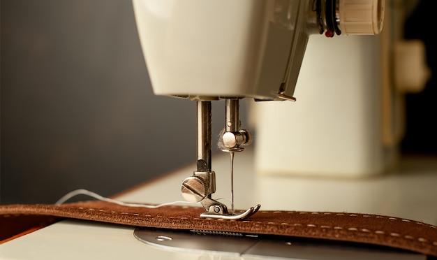 Achtergrondtype van naaimachine, het naaien van de leerriem. leeratelier.