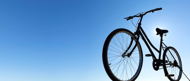 Achtergrondverlichting silhouet van een klassieke zwarte fietstocht. blauwe lucht op de achtergrond. panoramisch zicht. ruimte voor tekst. outdoor activiteiten concept.