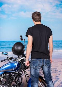 Achterk bezichtiging, van, jonge man, staand, naast, klassieke, blauwe, motorfiets, op, strand, en, geconfronteerd, water