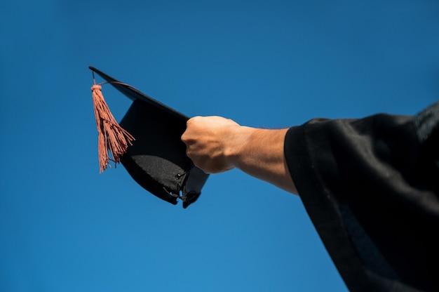 Achterk bezichtiging, van, man, in, afstuderen, toga, vasthouden, pet, staand, tegen, hemel