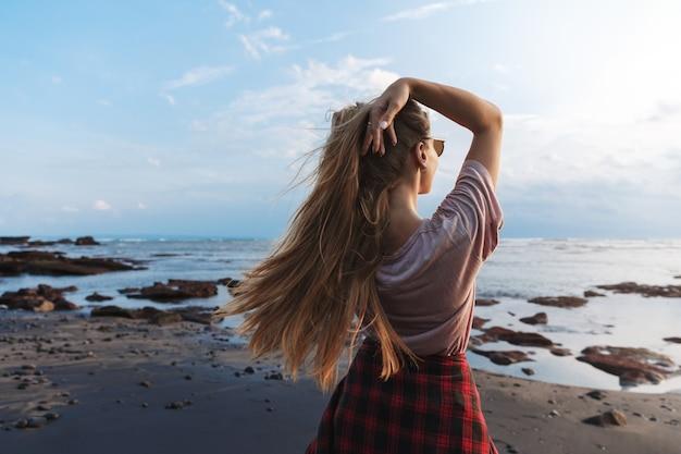 Achterkant bekijken een reizigersmeisje met lang haar, genietend van uitzicht op de blauwe oceaan op het zwarte vulkanische zandstrand.