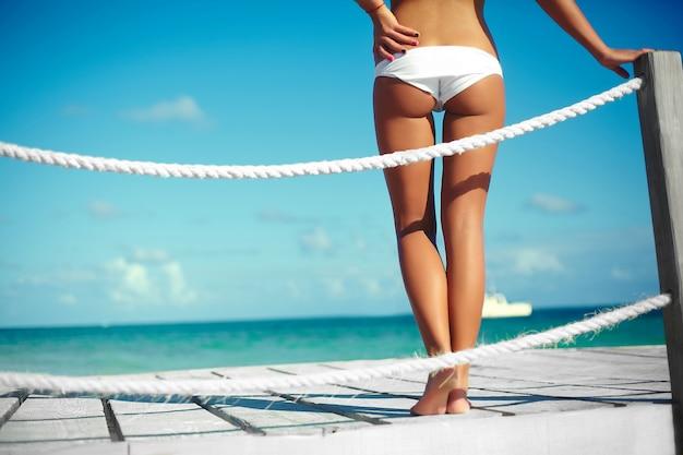 Achterkant glamour zonovergoten vrouw in witte lingerie op een pier