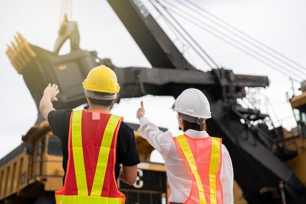Achterkant van arbeiders in de bruinkool- of kolenwinning met de vrachtwagen die kolen vervoert.