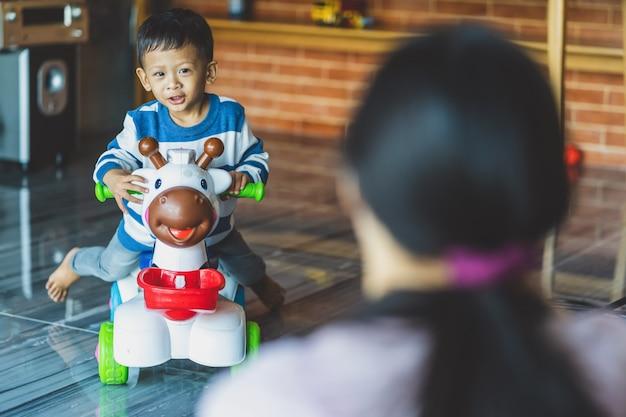 Achterkant van aziatische alleenstaande moeder met zoon spelen samen met speelgoed wanneer ze in een loft wonen
