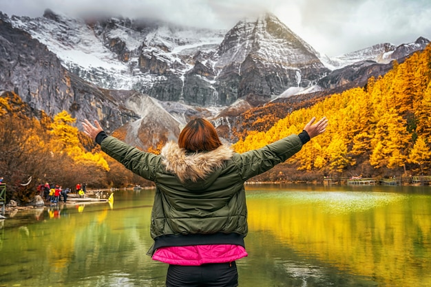 Achterkant van aziatische reizigersvrouw die en over het parelmeer met sneeuwberg kijken kijken in de herfstseizoen in yading natuurreservaat, china. reizen en toerisme, beroemde plaats en oriëntatiepuntconcept