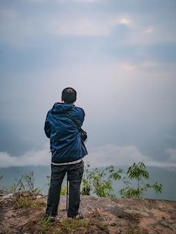 Achterkant van aziatische trekker met secnery uitzicht in de ochtend op phu kradueng mountain national park in loei city thailand.phu kradueng mountain national park de beroemde reisbestemming