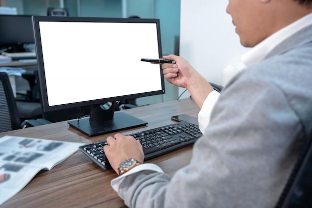 Achterkant van aziatische zakenman in formele pak met behulp van en wijst de pen naar computerscherm