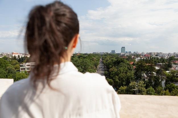 Achterkant van blanke vrouwelijke toursit die op het torenterras staat