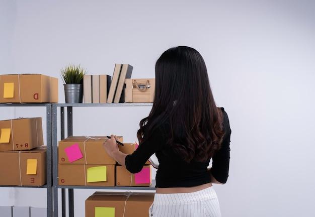 Achterkant van dame die bestelling en brievenbus controleert, voor verzending naar klant voorbereiden. e-commerce, online zaken