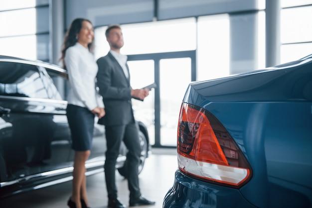 Achterkant van de blauw geschilderde auto. vrouwelijke klant en moderne stijlvolle bebaarde zakenman in de auto-salon