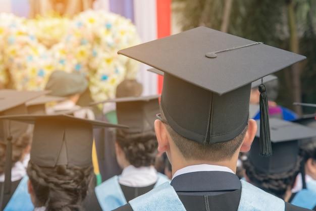 Achterkant van de hoed-man studeert af op de repetitiedag op de universiteit. close-up op afgestudeerde hoed: toekomstconcept