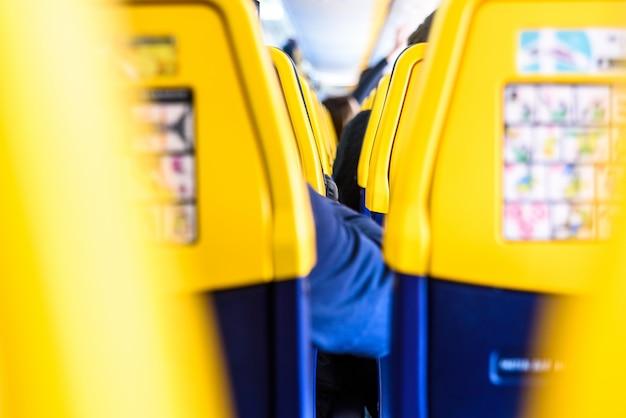 Achterkant van de stoelen van een boeing-vliegtuig met veiligheidsinstructies, verplicht lezen voor passagiers.