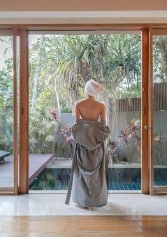 Achterkant van de vrouw die haar badjas uitdoet en naar het zwembad loopt.