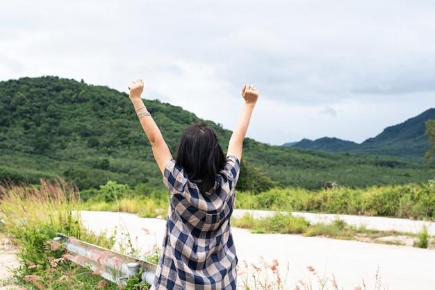Achterkant van de vrouw, het verhogen van handen omhoog in de lucht, zingen en symbool van het opladen van kracht uit de frisse natuur, uitzicht op het platteland