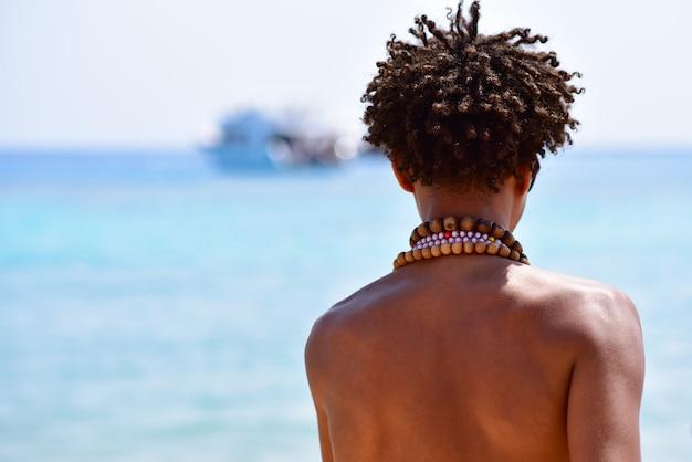 Achterkant van een afrikaanse man met een kralen van de zee