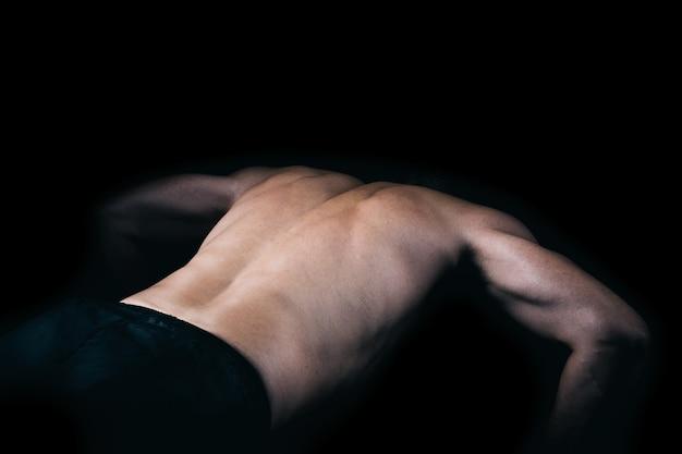 Achterkant van een gespierde man die pushups doet