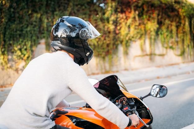 Achterkant van een man in een helm die een motorfiets op de weg bestuurt