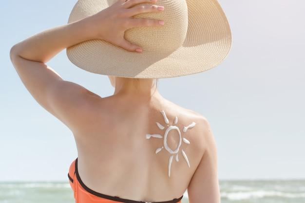 Achterkant van een meisje met een geschilderde crème zon