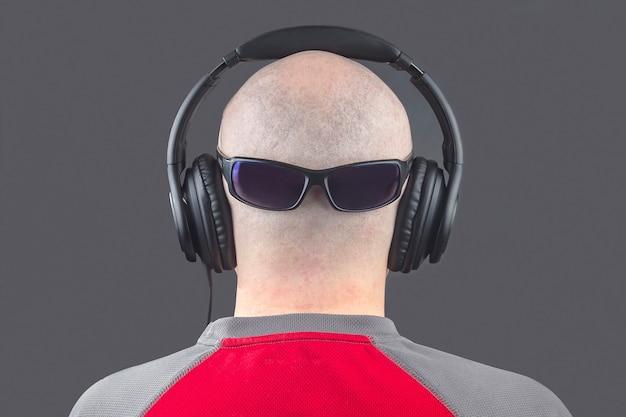 Achterkant van een naakte man die naar muziek luistert met een koptelefoon en een zonnebril op de rug