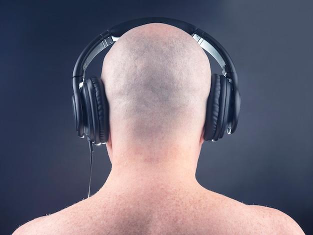 Achterkant van een naakte man, luisteren naar muziek met een koptelefoon op een donkere achtergrond