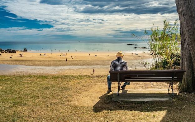 Achterkant van een senior man zittend op een bankje aan de kust van de zee