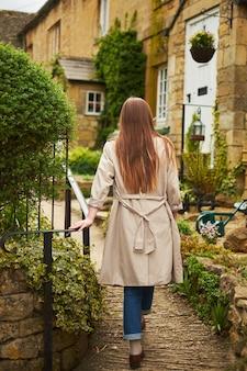 Achterkant van een vrouw die naar haar huis gaat. tegen de achtergrond van een oud huis in het dorp