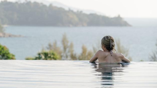 Achterkant van een vrouw in zwembad, zomervakantie.